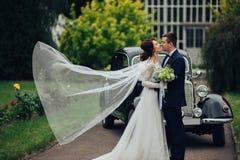 时髦的肉欲上摆在有boh的减速火箭的汽车附近的新娘和新郎 图库摄影