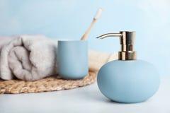 时髦的肥皂分配器、持有人与牙刷和毛巾在桌上 免版税库存图片