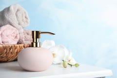 时髦的肥皂分配器、毛巾在柳条筐和花在桌上 库存照片