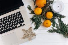 时髦的膝上型计算机和圣诞节桔子和金黄星和蜡烛 免版税库存照片