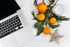 时髦的膝上型计算机和圣诞节桔子和金黄星和蜡烛 库存图片