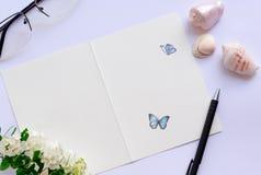时髦的舱内甲板放置与卡片空格插入您的文本,邀请,婚礼 贝壳,笔,玻璃,白花 图库摄影