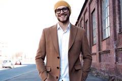 时髦的英俊的年轻人画象玻璃的与站立的刺毛户外 人佩带的夹克和衬衣 免版税库存图片