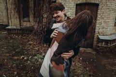 时髦的获得乐趣和笑在秋天公园的男人和妇女 Co 图库摄影