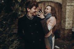 时髦的获得乐趣和笑在秋天公园的男人和妇女 Co 免版税库存图片