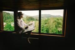 时髦的行家人在窗口有看法坐山和 免版税库存图片