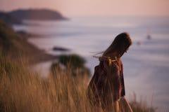 年轻时髦的行家女孩享受在观点的日落 有背包的旅行妇女 库存照片