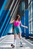 时髦的衣物和减速火箭的太阳镜路辗的年轻女人 库存照片
