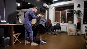 时髦的衣裳的一位成人美发师刮一个人的头,美发师用创造一种时兴的发型 股票录像
