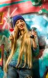 时髦的衣裳的时兴的美丽的女孩用一街道画背景伟大的糖果和杯在他的手上 免版税图库摄影
