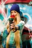 时髦的衣裳的时兴的美丽的女孩用一街道画背景伟大的糖果和杯在他的手上 图库摄影