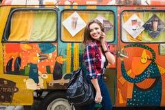 时髦的衣裳的年轻美丽的女孩在摆在城市街道的老打破的公共汽车前面 免版税库存图片