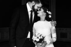 时髦的豪华拥抱在b的新娘和英俊的典雅的新郎 免版税库存照片