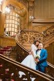 时髦的豪华摆在新娘和英俊的典雅的新郎握有花束的手在老木台阶 免版税库存照片