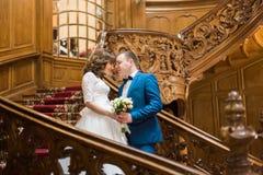 时髦的豪华摆在有花束的新娘和英俊的典雅的新郎面对面的举行的手在老木台阶 图库摄影