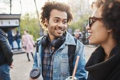 时髦的非裔美国人特写镜头画象有逗人喜爱的微笑和非洲的发型的谈话与兄弟姐妹,当获得乐趣时 免版税库存照片