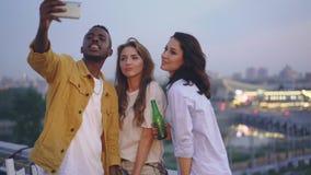 时髦的非裔美国人的人采取与逗人喜爱的白种人女孩的selfie在屋顶的露天党,年轻人使用 股票录像