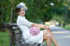 时髦的鞘礼服的美丽的新娘有bouqu的 库存照片