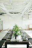时髦的饭食和桌,顶楼 顶楼样式的设计室 黑桌,椅子,盘,蜡烛 有绿色的瓶子 库存图片
