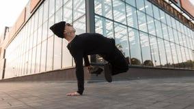 时髦的黑被编织的帽子的好年轻行家人在黑牛仔裤的太阳镜在跳舞在城市的时髦的运动鞋户外 免版税库存照片