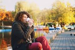 时髦的年轻人坐湖边在秋天公园和喝一些咖啡 免版税库存照片
