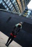 时髦的年轻哀伤的妇女画象黑外套和帽子的反对现代大厦 库存照片