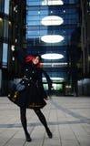 时髦的年轻愉快的妇女画象黑外套和帽子的反对现代大厦 免版税库存照片