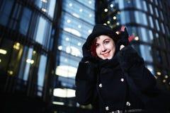 时髦的年轻愉快的妇女画象黑外套和帽子的反对现代大厦 免版税图库摄影