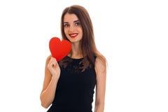 时髦的黑礼服的年轻可爱的深色的妇女有红色心脏的在她的看照相机和微笑的手上 免版税库存图片