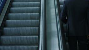 时髦的黑衣服的商人在自动扶梯提高 股票视频