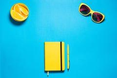 时髦的minimalistic女性时尚工作区 明亮的黄色玻璃和日志与笔, pirces桔子反对深深 库存图片