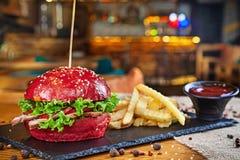 时髦红色小圆面包汉堡用猪肉供食与薯条和红色调味汁 不健康的便当 在餐馆内部的汉堡 库存图片