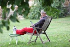 时髦老人读书ebook在庭院里 图库摄影