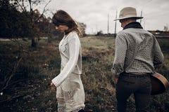 时髦行家夫妇摆在 帽子的人有吉他和他的bo的 库存图片