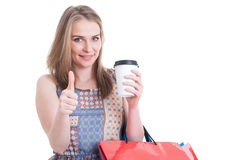 时髦逗人喜爱的女性举行的咖啡杯和运载的购物袋 免版税图库摄影