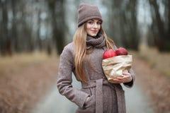 时髦都市的时髦的白肤金发的妇女穿破摆在冷气候有红色苹果包裹的森林公园胡同  秋天心情概念 图库摄影