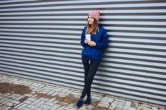 时髦都市的时髦的运动的深色的妇女穿破摆在与大白色一次性杯子秸杆冷的多雨秋天天反对小条 免版税库存照片