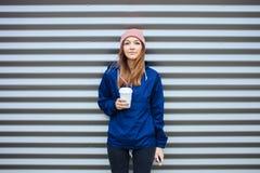 时髦都市的时髦的运动的深色的妇女穿破摆在与大白色一次性杯子秸杆冷的多雨秋天天反对小条 库存图片