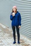 时髦都市的时髦的运动的深色的妇女穿破摆在与大白色一次性杯子秸杆冷的多雨秋天天反对小条 图库摄影