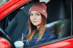时髦都市的时髦的运动的深色的妇女穿破驾驶有大白色一次性杯子秸杆冷的秋天天葡萄酒filt的一辆汽车 库存照片