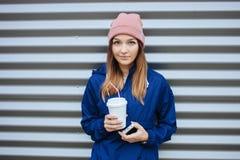 时髦都市的时髦的运动的深色的微笑的妇女穿破再摆在与大白色一次性杯子秸杆冷的多雨秋天天 库存图片
