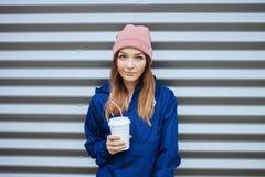 时髦都市的时髦的运动的深色的微笑的妇女穿破再摆在与大白色一次性杯子秸杆冷的多雨秋天天 库存照片