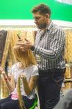 时髦主要理发师做一时髦的updo年轻白肤金发的妇女头发显示 免版税库存图片
