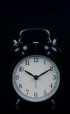时间到-在黑背景隔绝的闹钟身分 库存照片