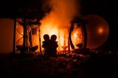 时间和爱概念 玩具陶瓷形象剪影拥抱在黑暗的滴漏之间的点燃了与雾的背景 免版税图库摄影