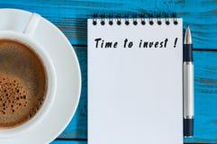 时刻投资-在笔记薄的通知在与早晨咖啡杯的蓝色木桌上 储款,货币业务概念 图库摄影