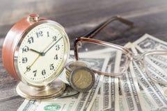 时间是金钱与老葡萄酒时钟、美金、眼镜和欧洲硬币的财务概念 免版税库存图片