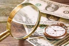 时间是金钱与老葡萄酒时钟、美金和放大镜的财务概念在木桌上 库存图片