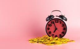 时间是金钱,在闹钟的金子在桃红色 库存图片