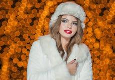 时兴的室外夫人佩带的毛皮的盖帽和的外套。年轻美丽的妇女画象冬天样式的。女孩的明亮的图片 免版税库存图片